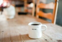 """Background blurred of a wooden table. In the foreground is a white coffee cup that says, """"Begin."""""""